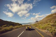 Pares novos entusiasmado que conduzem para baixo em uma estrada aberta Imagens de Stock
