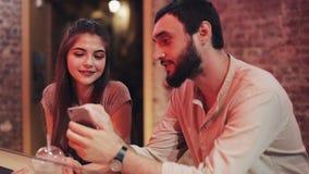 Pares novos felizes com assento de fala e bebendo do smartphone da bebida na barra Amigos que usam o smartphone do telefone celul video estoque
