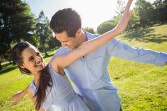 Pares novos felizes com os braços estendido no parque Fotos de Stock