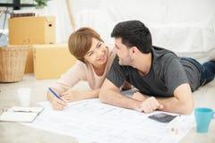 Pares novos felizes com os modelos que planeiam sua casa nova imagens de stock