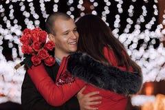 Pares novos felizes com ramalhete das rosas em uma data imagem de stock