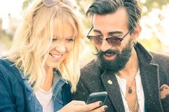 Pares novos felizes com a roupa do vintage que tem o divertimento com telefone Fotografia de Stock