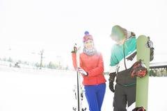 Pares novos felizes com snowboard e esquis na neve Imagens de Stock Royalty Free