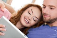 Pares novos felizes com tabuleta digital Foto de Stock