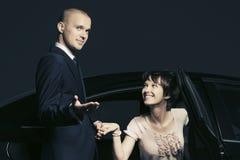 Pares novos felizes da forma com um carro na noite fotos de stock royalty free