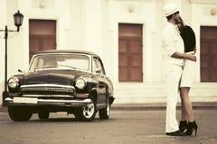 Pares novos felizes da forma no amor ao lado do carro do vintage Fotos de Stock Royalty Free