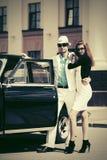 Pares novos felizes da forma no amor ao lado do carro do vintage Foto de Stock