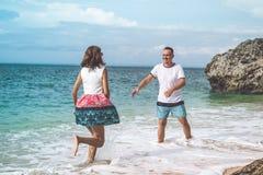 Pares novos felizes da lua de mel que têm o divertimento na praia Oceano, férias tropicais na ilha de Bali, Indonésia foto de stock royalty free