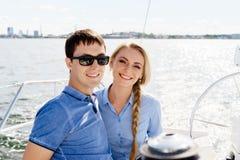 Pares novos felizes e bonitos que têm um resto em um iate Trave Fotos de Stock Royalty Free