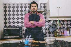Pares novos felizes e sorrindo que cozinham o alimento na cozinha em ho imagem de stock