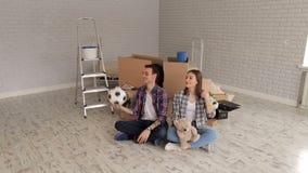 Pares novos felizes em camisas de manta em um apartamento novo entre caixas de cartão filme