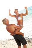 Pares novos felizes na praia Imagens de Stock