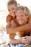 Pares novos felizes na praia Foto de Stock