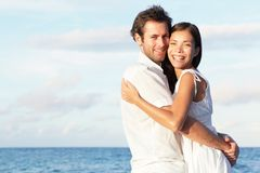 Pares novos felizes na praia fotografia de stock royalty free