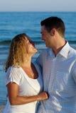 Pares novos felizes na praia Imagens de Stock Royalty Free