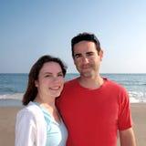 Pares novos felizes na praia Imagem de Stock