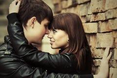 Pares novos felizes no amor na parede de tijolo Imagens de Stock