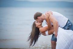 Pares novos felizes no amor que anda na praia Fotos de Stock