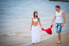 Pares novos felizes no amor que anda na praia Imagens de Stock Royalty Free
