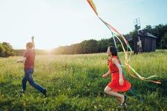 Pares novos felizes no amor que corre um papagaio no campo Dois, homem e mulher sorrindo e descansando no lado do país imagem de stock