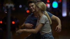 Pares novos felizes no amor que fala e que abraça na rua da cidade na noite, romance filme