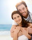 Pares novos felizes que abraçam na praia do verão Foto de Stock
