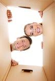 Pares novos felizes que abrem uma caixa da caixa e que olham para dentro Imagens de Stock Royalty Free
