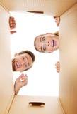 Pares novos felizes que abrem uma caixa da caixa e que olham para dentro Fotos de Stock Royalty Free