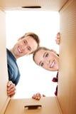 Pares novos felizes que abrem uma caixa da caixa e que olham para dentro Imagens de Stock