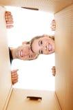 Pares novos felizes que abrem uma caixa da caixa e que olham para dentro Foto de Stock