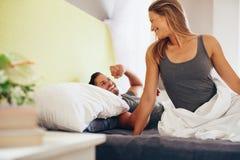 Pares novos felizes que acordam na manhã na cama Fotos de Stock Royalty Free