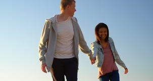 Pares novos felizes que andam em conjunto na praia 4k vídeos de arquivo