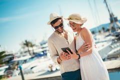 Pares novos felizes que andam pelo porto usando a tabuleta digital foto de stock royalty free
