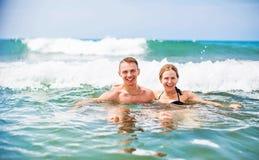 Pares novos felizes que apreciam o mar foto de stock royalty free