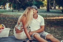 Pares novos felizes que beijam durante o piquenique rom?ntico em um parque imagens de stock royalty free