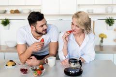 pares novos felizes que comem morangos imagem de stock royalty free