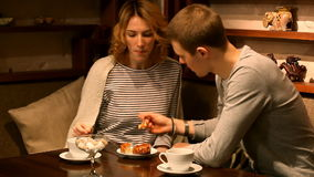 Pares novos felizes que comem o bolo e que bebem o chá O indivíduo alimenta a menina filme
