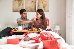 Pares novos felizes que comem um café da manhã surpreendente na cama Imagens de Stock