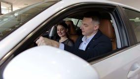 Pares novos felizes que compram um carro em uma feira automóvel moderna Close-up filme