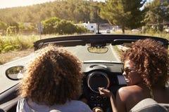 Pares novos felizes que conduzem em um carro superior aberto, Ibiza, Espanha imagem de stock