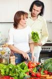Pares novos felizes que cortam o aipo para a salada na cozinha home Fotografia de Stock