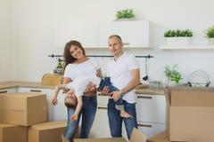 Pares novos felizes que desembalam ou caixas de embalagem e que movem-se em uma casa nova fotografia de stock royalty free