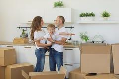 Pares novos felizes que desembalam ou caixas de embalagem e que movem-se em uma casa nova imagem de stock
