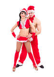 Pares novos felizes que desgastam a roupa de Papai Noel Imagem de Stock