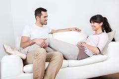 Pares novos felizes que encontram-se ele o sofá Fotografia de Stock Royalty Free