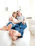 Pares novos felizes que encontram-se junto no sofá Imagem de Stock Royalty Free