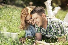 Pares novos felizes que encontram-se na grama, olhando o portátil e o SMI Foto de Stock Royalty Free