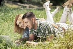 Pares novos felizes que encontram-se na grama, olhando o portátil e o SMI Foto de Stock