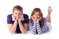 Pares novos felizes que encontram-se para baixo no assoalho Imagem de Stock Royalty Free
