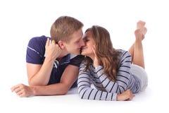 Pares novos felizes que encontram-se para baixo no assoalho e no beijo Imagem de Stock Royalty Free